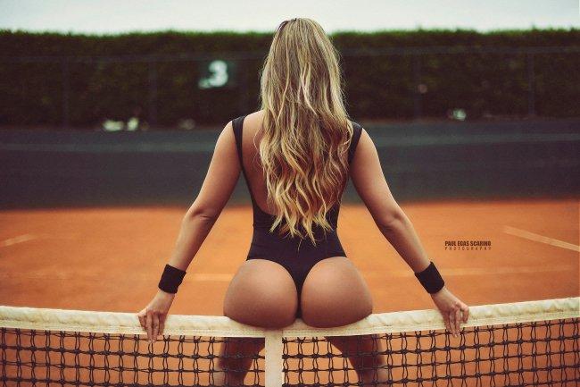 Девушка в черном боди позирует на теннисном корте