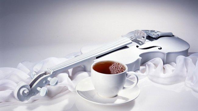 На белой драпировке стоит чашка чая и белая скрипка