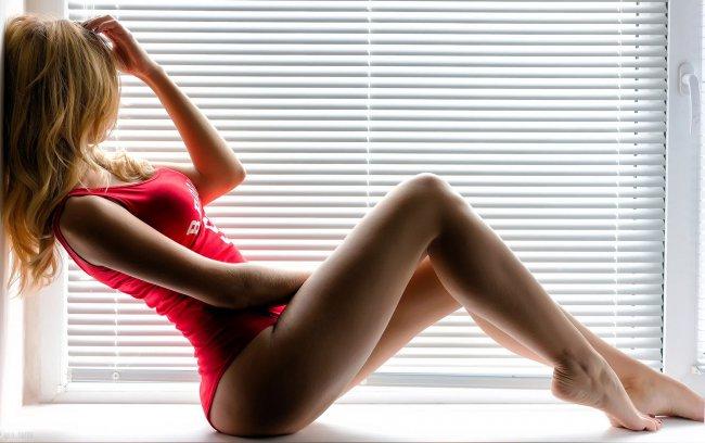 Блондинка позирует возле окна