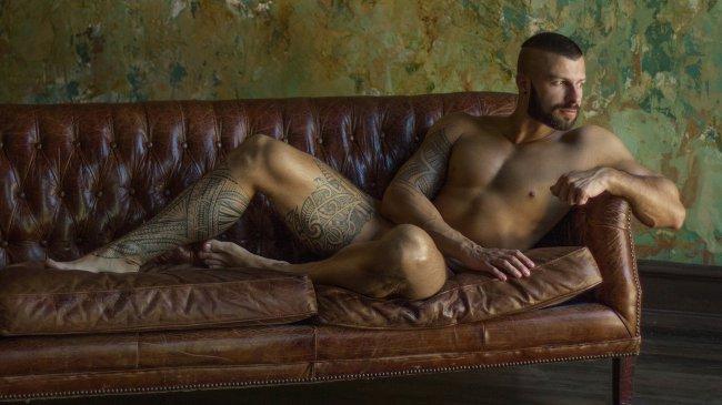 Обнаженный мужчина с татуировками лежит на кожаном диване