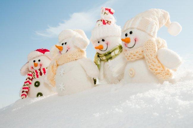 Четыре веселых снеговика в вязанных шарфах и шапках