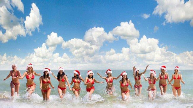 Девушки в красных купальниках и шапочках Санты выбегают из океана