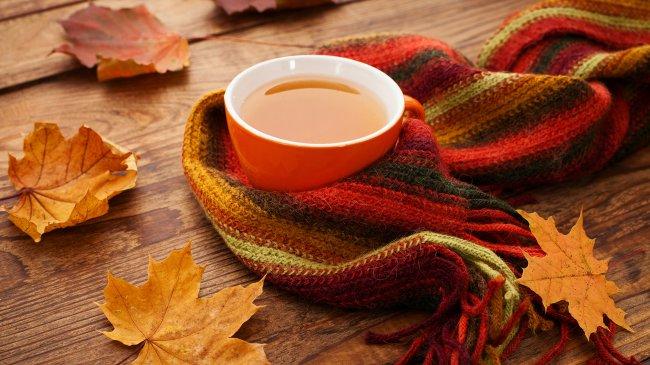 Осенние листья, шапф и чашка чая на деревянном столе