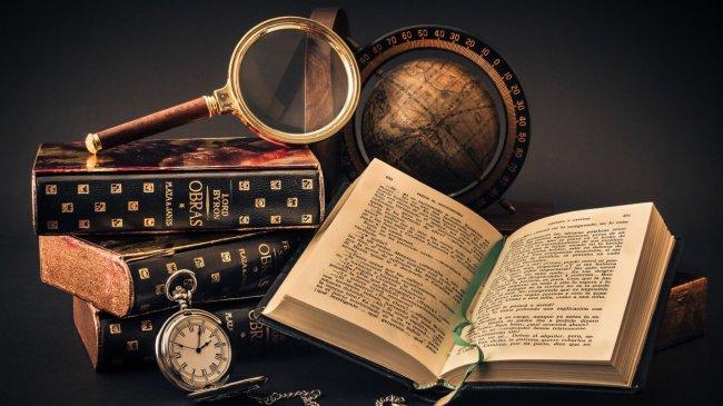 На столе книги, глобус, часы и увеличительное стекло