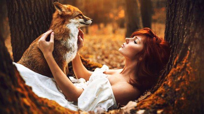 Рыжая девушка с лисой в осеннем лесу