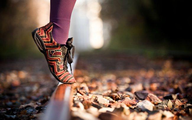 Девушка стоит одной ногой на железнодорожных рельсах