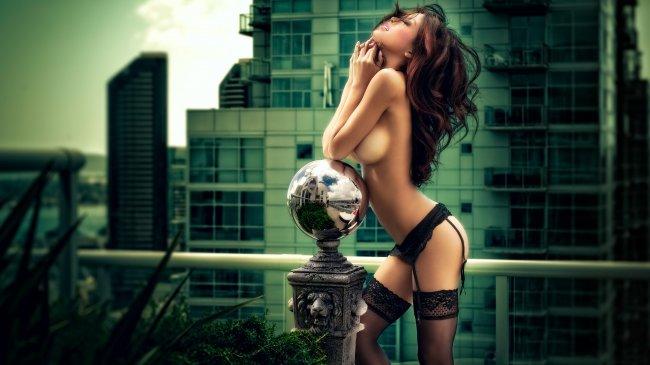 Полуобнаженная девушка на балконе небоскреба