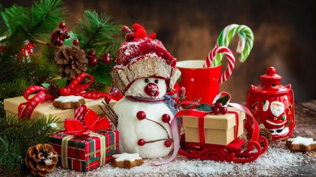 Игрушечный снеговик и подарки стоят под елкой