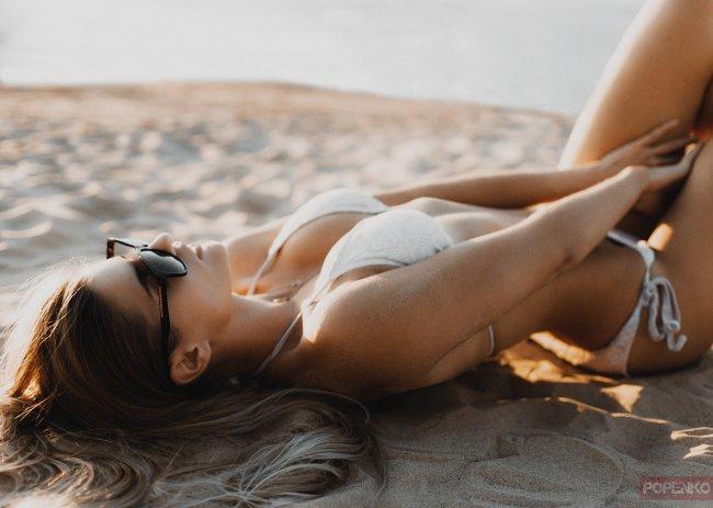 Девушка в очках лежит на песке