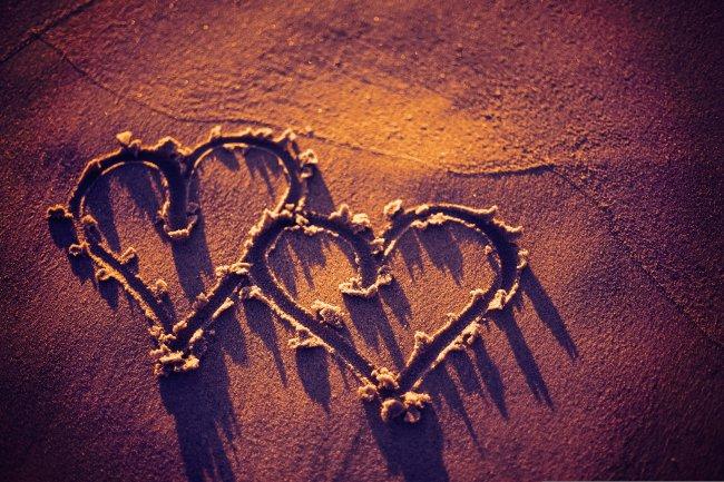 Два сердца на песчаном пляже под солнцем на рассвете