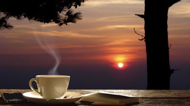 Чашка с горячим кофе стоит на столе на фоне заката