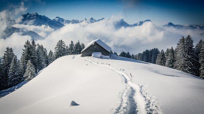Домик на холме среди скалистых снежных гор