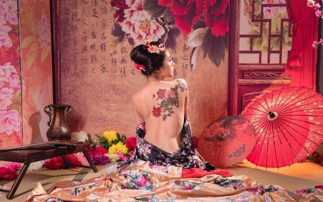 Обнаженная гейша с татуировкой на спине