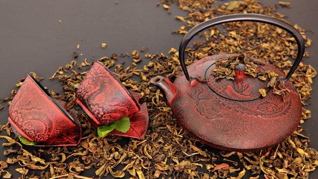 Чайник с чашками и рассыпанные чайные листья