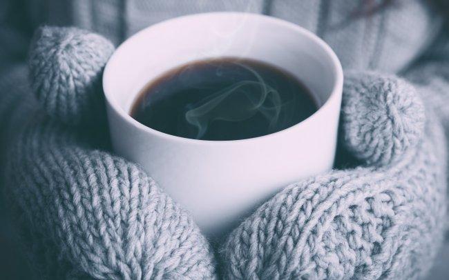 Девушка в варежках держит бокал с горячим кофе