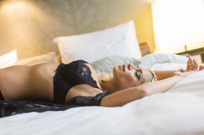 Блондинка лежит на кровати