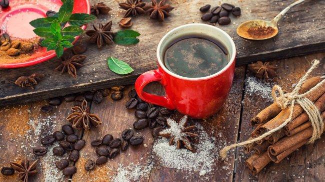 Чашка кофе стоит на столе с рассыпанными специями