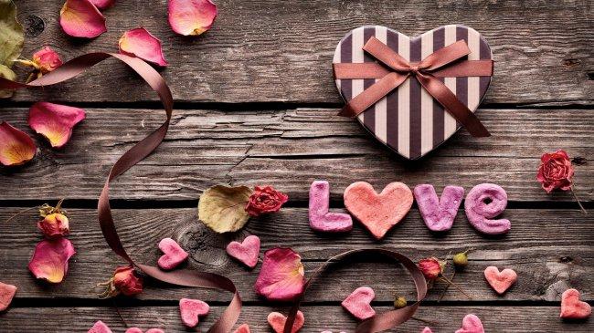 Сердечки и лепестки роз на деревянной поверхности