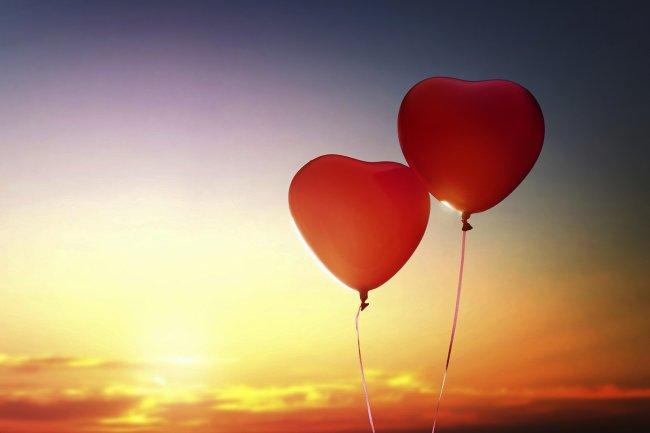 Два воздушных шара в виде сердца в небе