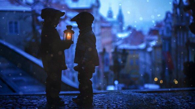 Два мальчика с фонарем на вечерней улице Праги