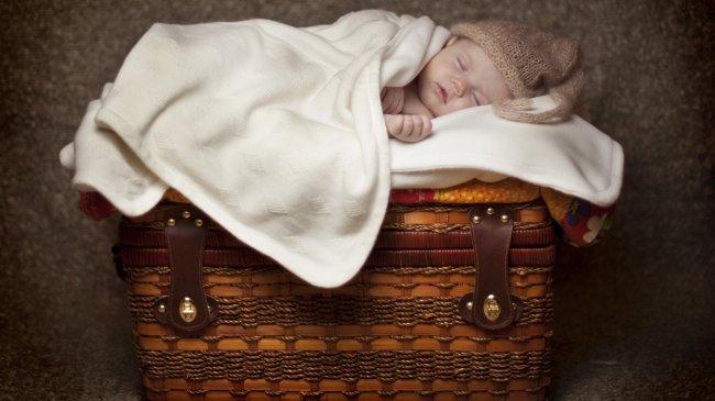Спящий младенец на плетеной корзине