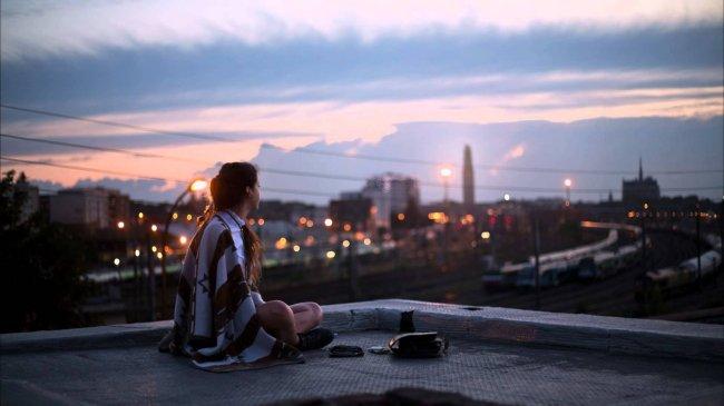 Девушка сидит в одиночестве на крыше