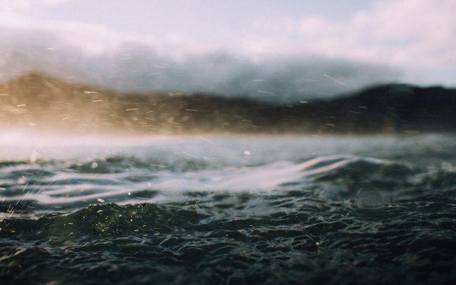 Брызги морской воды на фоне холмистого берега