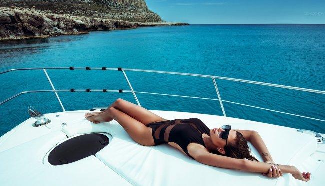 Девушка в черном боди на белоснежной яхте