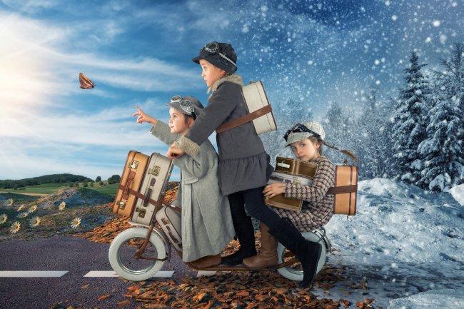 Трое детей с чемоданами едут на велосипеде
