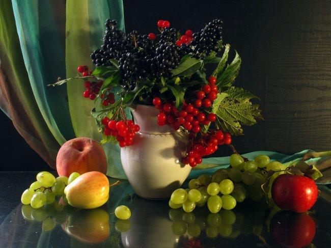 На столе лежат фрукты и стоит ваза с ягодами