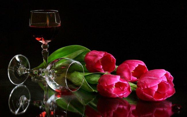 Три тюльпана лежат возле бокалов