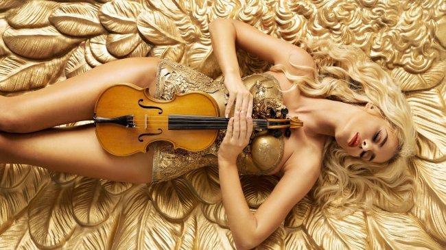 Сексуальная девушка лежит со скрипкой