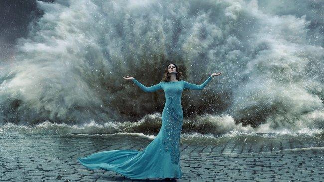 Девушка в длинном платье на фоне разбивающейся волны