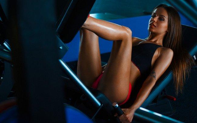 Девушка качает ноги в спортзале