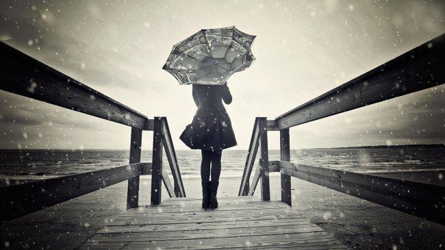 Девушка с зонтом у берега моря