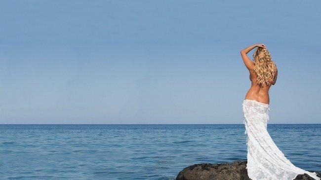 Блондинка топлес смотрит на море