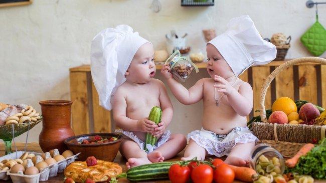 Два маленьких поваренка среди продуктов