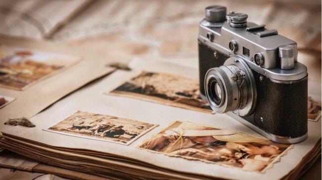 Фотоаппарат возле альбома с фотографиями