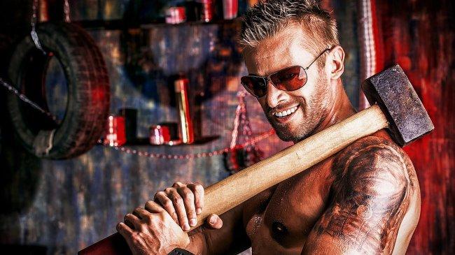 Мужчина с татуировками держит кувалду