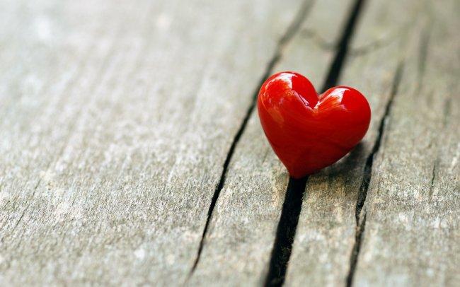 Маленькое красное сердце на деревянной поверхности