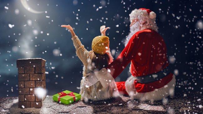 Санта Клаус с девочкой на крыше дома