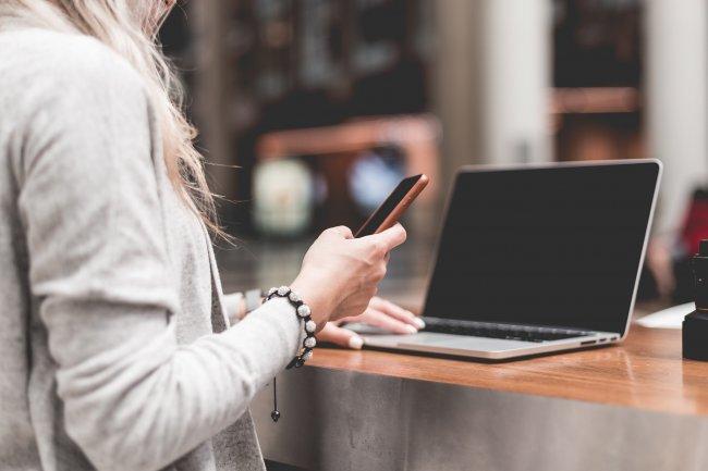 Женщина, держащая iPhone в правой руке работая за ноутбуком