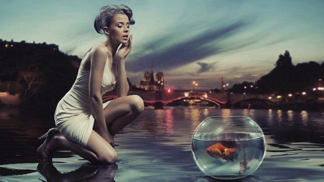 Девушка возле аквариума с золотой рыбкой
