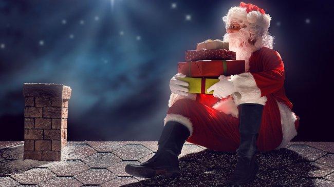 Сантаклаус с подарками сидит у дымохода