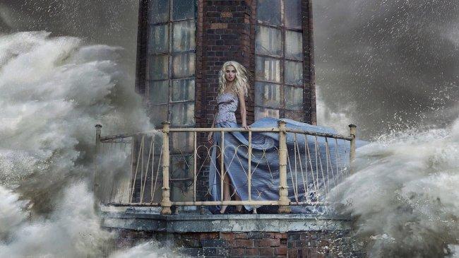 Блондинка в шторм стоит на маяке