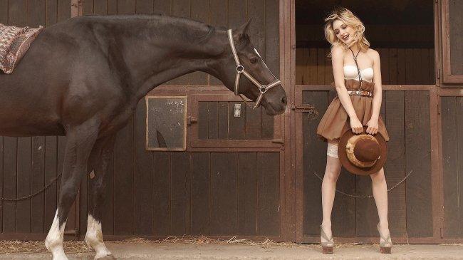 Симпатичная блондинка на конюшне