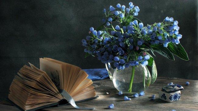 Цветы в кувшине рядом с открытой книгой