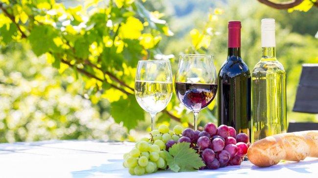 На столе две бутылки с красным и белым вином