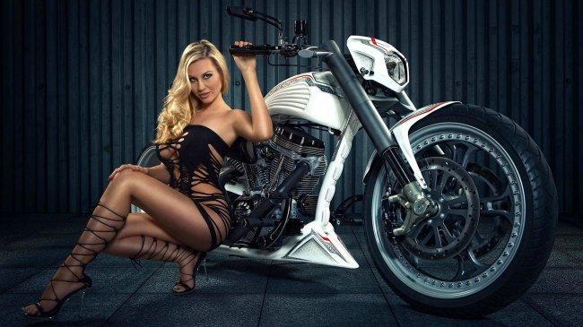 Девушка в откровенном костюме сидит возле мотоцикла