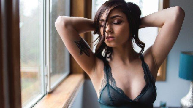 Брюнетка с татуировкой на руке у окна